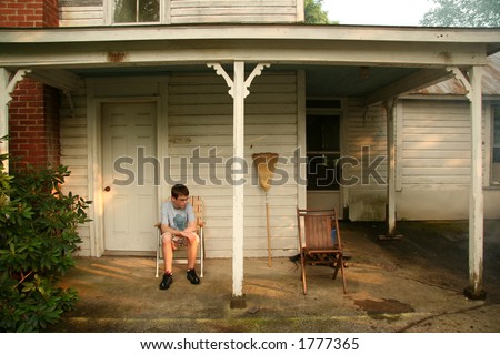 Boy sitting on porch looking down.