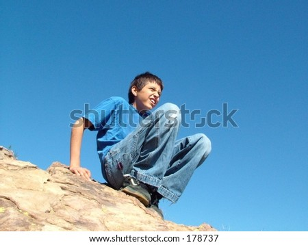 Boy sitting on rock against deep blue sky at Vasquez Rock, California