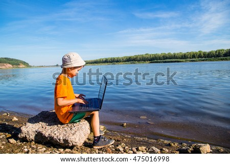 boy sitting on the beach with a notebook #475016998