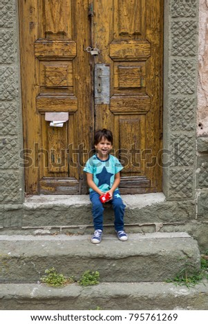 boy sitting on the stairs in front of an old door and happy with life.