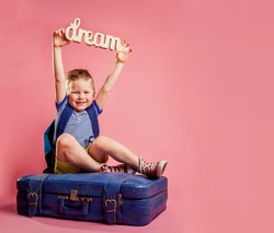 Boy sitting on the travel bag and dreaming. Dream of future. Child with backpack and sleepers want to go on summer vacation