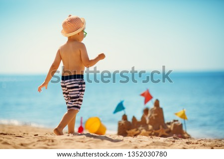 boy sitting smiling at the beach #1352030780