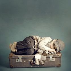 boy sleeping on a suitcase