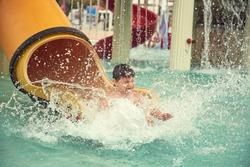 Boy sliding down slide in waterpark.