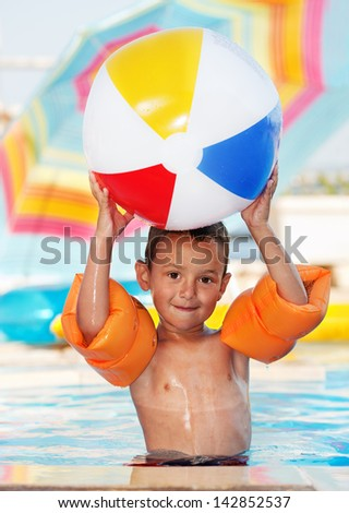 Boy smiling and playing with ball in to a swimming pool