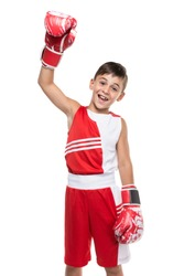 boy sportsman in boxing gloves raised one hand and demonstrates victory, smiles, sport concept