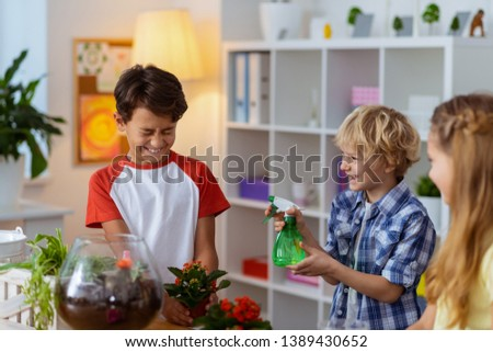 Boy sprinkling water. Blonde funny boy sprinkling water on his classmates after watering plants at ecology class