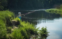 Boy standing at river bank catching fish on sunny summer day nature background. Little fisherman holding fishing rod alone in countryside. Happiness active lifestyle summertime vacation