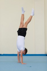 boy stands on his hands in the gym.