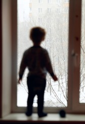 Boy stands on the windowsill and looking through the window.
