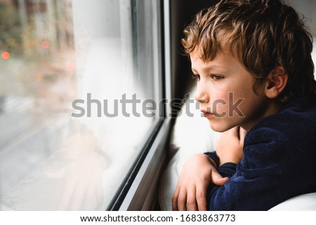 Boy stays home bored by school closings due to covid pandemic. Foto stock ©