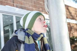 Boy sticking his tongue to a flag pole