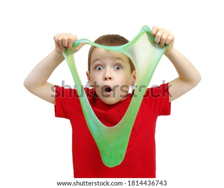 Boy stretches slime toy in hands and looks through it. Kid playing on a white background ストックフォト ©