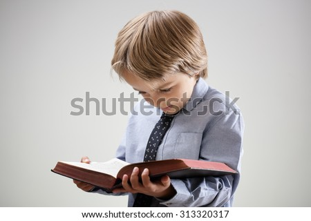 Boy studying and reading a book or bible isolated concept for education, religion or homework