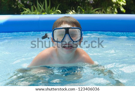 Boy swimming in garden pool with mask and snorkel