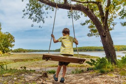 boy swinging on a handmade swing. old  tree with swing on a shore river