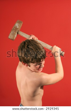 boy swinging sledge hammer vertical