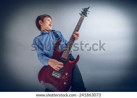 boy teenager European appearance brown emotionally plays guitar cross process