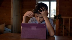 boy think at the table near the tablet, clutching his head, insoluble situation