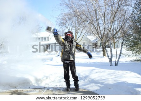 Boy throwing a pan of boiling water that freezes into ice crystals on contact with the sub zero air