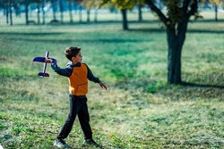 Boy Throwing Airplane Gliding Toy in the Park.
