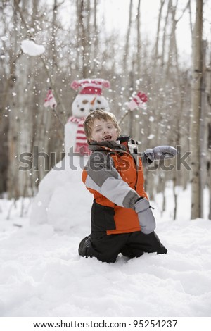 Boy throwing snowball in front of snowman