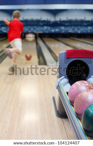 Boy throws ball in bowling; Focus on number of colorful balls; back of boy