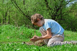 boy trying to take flame by primitive way by stick in wood
