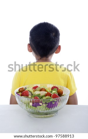 Boy turning his back to fruit and vegetable salad shot in studio isolated on white