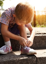 Boy tying the laces on sneakers sitting on the steps