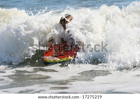Boy using a body board with a wave crashing over him