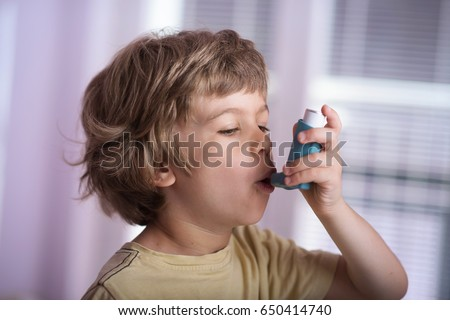Boy using asthma inhaler to treat inflammatory disease, wheezing, coughing, chest tightness and shortness of breath. Allergy treating concept.