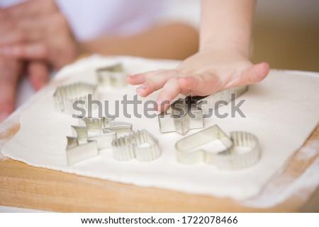 Boy using cookie cutter in dough, close up