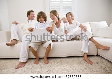 Boy using laptop sitting with family on white sofa