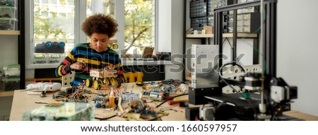 Boy using screwdriver while fixing bolts on a robot vehicle. Smart kids and STEM education. Robotics and software engineering for elementary students. Web Banner