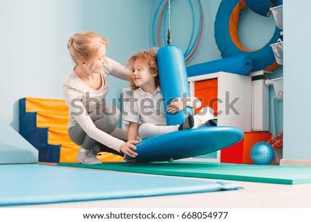 Boy using sensory integration equipment and a woman helping him #668054977