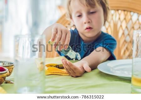 Boy using wash hand sanitizer gel in the cafe.