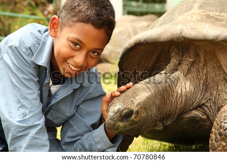Boy visits Jonathan the tortoise on St Helena. Jonathan the famous giant tortoise who is estimated to be two hundred years old