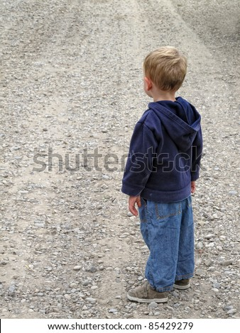 Boy waiting on gravel road