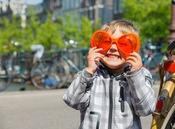 Boy walking in orange glasses for Dutch Queensday on the Amsterdam street