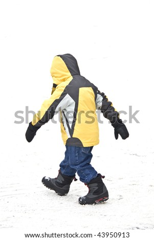 Boy walking in winter snow with yellow jacket jeans and boots.