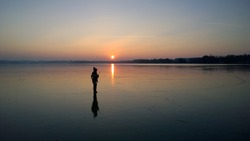Boy walking on frozen Lake Woerthsee at sunset, Bavaria, Germany, Europe