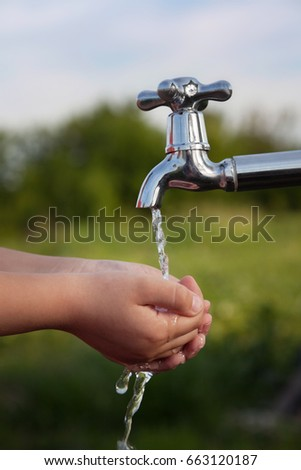boy washes his hand under the faucet in the garden #663120187