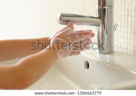 Boy washing hands at sink, Den Haag, Netherlands