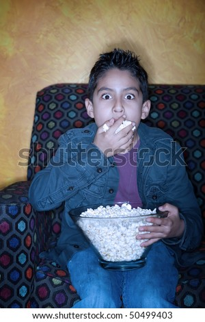 Boy watching a scary movie while eating popcorn