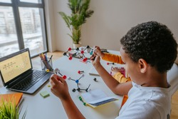 Boy watching online lesson chemistry science holding molecular model at home. Selective focus on the boy.