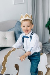 Boy wearing a crown (not a coronavirus), a happy boy riding a horse like a prince, a concept of creativity and development for staying at home.