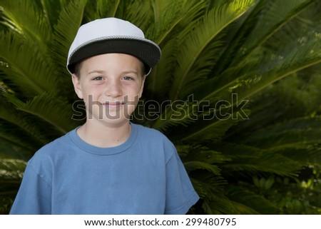 Boy wearing baseball hat standing by palm