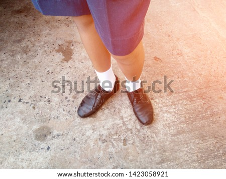 Boy wearing black leather shoes, white socks, standing on cement floor #1423058921