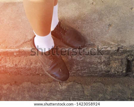 Boy wearing black leather shoes, white socks, standing on cement floor #1423058924
